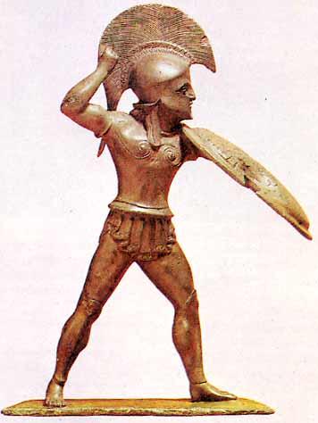Αγαλματίδιο Έλληνα πολεμιστή από την Δωδώνη, σήμερα βρίσκεται στο Μουσείο του Βερολίνου. Η κινησιολογία του αγάλματος μας οδηγεί σε κάποια συμπεράσματα πρακτικής φύσεως. Η ασπίδα δεν είναι παράλληλη προς το σώμα αλλά έχει τεθεί υπό γωνία στον κατακόρυφο άξονα κίνησης. Αυτή η στάση σίγουρα θα κρατούσε τον αντίπαλο σε κάποια απόσταση καθώς η ασπίδα γίνονταν προέκταση του βραχίονα. Η ασπίδα κάλλιστα θα μπορούσε να χρησιμεύει και ως επιθετικό όπλο, δηλ. ένα είδος εμβόλου. Ο Οπλίτης έχει προωθημένη την αριστερή πλευρά του έτσι ώστε να είναι ικανός να κρατήσει την απαιτούμενη ισορροπία αλλά και να κινηθεί σταθερά προς τα εμπρός. Η δεξιά πλευρά είναι εκτεθειμένη και τραβηγμένη προς τα πίσω ενώ το δεξί χέρι βρίσκεται ανασηκωμένο στο ύψος του κεφαλιού έτοιμο να πλήξει με το δόρυ (;) τον αντίπαλο πάνω από το ύψος της ασπίδας. Ένα ανακύπτον ερώτημα είναι κατά πόσο μία τέτοια στάση σώματος θα ήταν δυνατόν να αποδοθεί στις πρώτες σειρές μιας οπλιτικής παράταξης. Η στάση του αγαλματιδίου αποθανατίζει μια μονομαχία Οπλίτη της πρώτης σειράς και αν ναι σε ποιο βαθμό ήταν δυνατόν να επιτευχθεί ωθισμός υπό τέτοιες συνθήκες; Τέτοιου είδους ερωτήματα μονάχα η πειραματική αρχαιολογία μπορεί να δώσει σαφής και συγκεκριμένες απαντήσεις. Image may be copyrighted.
