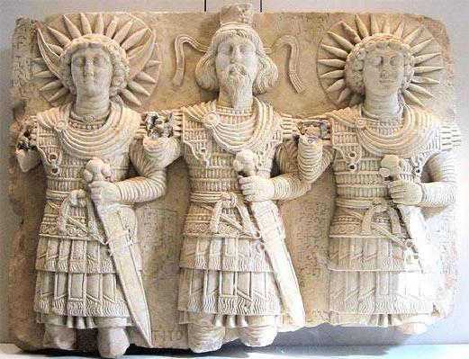 Ανάγλυφο με  τριάδα Παλμυρικών θεών χρονολογημένη περίπου το πρώτο μισό του πρώτου μεταχριστιανκού αιώνα. Στην μέση βρίσκεται ο μέγιστος θεός της Παλμύρας Bel φορώντας κάλαθο και διάδημα, στα δεξιά του ο θεός του φεγγαριού Aglibol και στα αριστερά του ο ηλιακός θεός Jarhibol. Η στρατιωτική εξάρτηση είναι Ελληνιστικού τύπου με πολλά Παρθικά ενδυματολογικά επιμέρους στοιχεία.Γενικά οι Θεοί των Αλεξανδρινών κέντρων φορούν ομοιόμορφους Ελληνιστικούς λινοθώρακες με ελασμάτινη ενίσχυση  κάτι που υπονοεί τυποποιημένη παραγωγή από κρατικά εργαστήρια. Η εξάρτηση λειτουργεί με αποτρεπτική σημασία καθώς επιδεικνύει την ετοιμότητά τους να υπερασπιστούν τις εκάστοτε Ελληνιστικές συγκεντρωτικές ηγεμονίες. Στην Ελληνιστική περίοδο οι Θεοί θα χάσουν οριστικά την Θεϊκή τους γύμνια που απολάμβαναν στην Κλασσική Αρχαιότητα. Ενδιαφέρον παρουσιάζει το γεγονός πως πριν την έλευση του Αλεξάνδρου στην Εγγύς Ανατολή οι ντόπιοι θεοί δεν εμφανίζονται με στρατιωτική περιβολή.