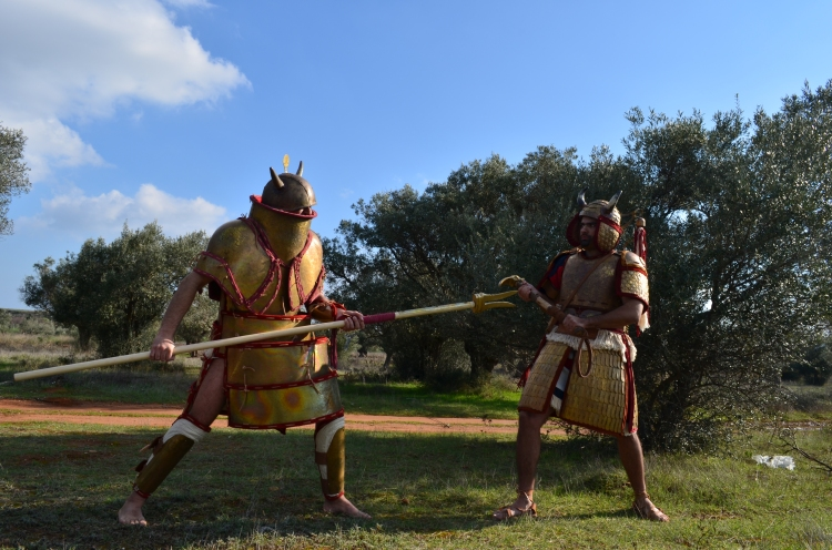 Pic1. The Mycenaean Warrior is taking an aggressive stance, taking advantage of the long naytiko xisto, capable of delivering devastating hits to the opponent. The opponent is armed with a heavy axini, ideal weapon to grab the plate armor and submit his opponent. Please pay attention on how the plate armor behave, as it easily follows the movements and does not restrict the Warrior... it was build in an ingenious way to provide total protection, at the same time it was engineered so that was able to totally expand and close (return to the original shape) instantly and effortlessly... Association of Historical Studies KORYVANTES