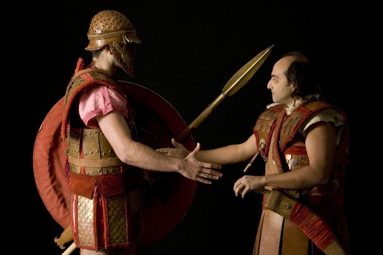 Αναπαράσταση Οπλιτών της πρώιμης Κλασσικής περιόδου. Ανάλογου τύπου σύνθετοι θώρακες χρησιμοποιούταν πιθανώς και από Σπαρτιάτες των Περσικών Πολέμων. Θεωρούταν ατίμωση για έναν προδότη να φέρει όπλα και η Πολιτεία του τα έπαιρνε για να τα δώσει σε Οπλίτες που πολεμούσαν στην πρώτη γραμμή. Η εικόνα αναπαριστά τη στιγμή που βαριά θωρακισμένος Οπλίτης αποδίδει τον δερματοθώρακα ενός προδότη Αριστοκράτη τοξότη σε άλλον Οπλίτη για να τον φέρει στη μάχη. Σύλλογος Ιστορικών Μελετών ΚΟΡΥΒΑΝΤΕΣ. Φώτο:  Ανδρέας Σμαραγδής